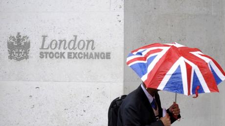 Un homme s'abrite de la pluie alors qu'il passe devant l'immeuble de la Bourse de Londres (illustration).