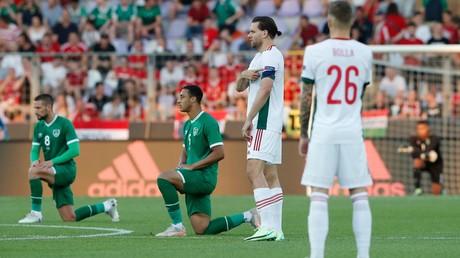 Des joueurs de l'équipe d'Irlande, le genou à terre, et des joueurs hongrois, à Budapest, le 8 juin 2021.