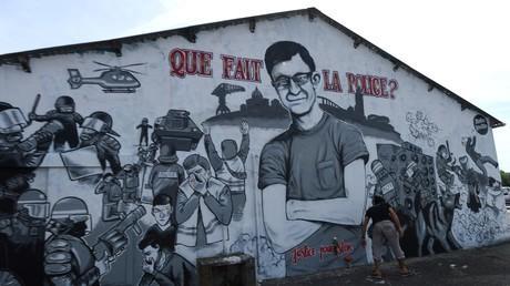 Une femme marche devant une freque murale représentant un portrait de Steve Maia Canico le 3 août 2019, à Nantes.
