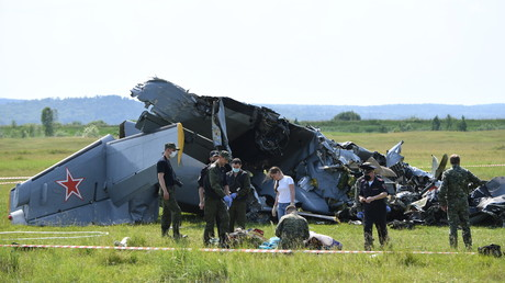 Des policiers et des inspecteurs russes devant les débris de l'appareil, près de l'aérodrome de Tanay, en Russie, le 19 juin 2021.
