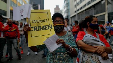 Une partisane du président vénézuélien Nicolas Maduro tient une pancarte indiquant «Les sanctions sont un crime» lors d'une marche à l'occasion du 1er Mai à Caracas, Venezuela, le 1er mai 2021.