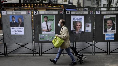 Un homme passe devant des affiches électorales, à Paris, le 24 juin 2021.