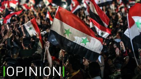 Des Syriens affichent leur drapeau dans les rues de Damas le 27 mai, au lendemain de l'élection présidentielle.