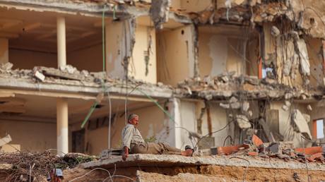 Un ouvrier palestinien se repose au milieu des ruines d'un immeuble de Gaza, le 30 juin 2021.
