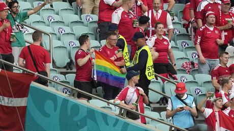 Des stadiers interviennent auprès d'un supporter danois qui brandit un drapeau arc-en-ciel avant le match de football entre la République tchèque et le Danemark au stade olympique de Bakou, le 3 juillet 2021.