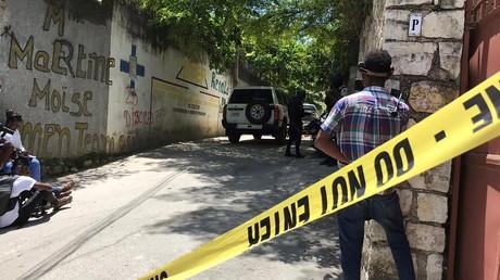 Des journalistes se tiennent à côté d'un cordon de police près de la résidence du président haïtien Jovenel Moise après qu'il a été abattu par des assaillants non identifiés, à Port-au-Prince.