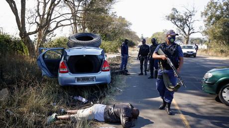 Des policiers procédant à des arrestations pendant les violences qui ont éclaté à la suite de l'emprisonnement de l'ancien président sud-africain Jacob Zuma, à Cato Ridge, en Afrique du Sud, le 14 juillet 2021.