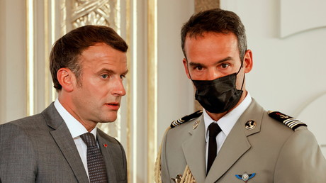 Le président français Emmanuel Macron échange avec son aide de camp lors d'une cérémonie au Palais de l'Elysée le 19 juillet 2021 (image d'illustration).