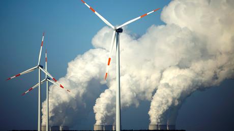 De la vapeur s'échappe des tours de refroidissement de la centrale à charbon (lignite) de Vattenfall Jaenschwalde derrière des éoliennes, près de Cottbus en Allemagne (image d'illustration).
