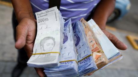 A Caracas, le 5 août 2021, un homme présente un échantillon de bolivars, la monnaie vénézuélienne, d'une valeur comprise entre 0,01 et 0,20 euros (illustration).