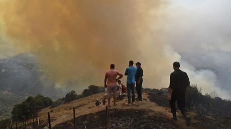 Des villageois se rassemblent devant de la fumée issue d'un feu de forêt, près de Tizi-Ouzou, le 12 août 2021 (image d'illustration)