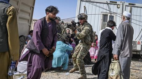Un soldat américain pointe son arme vers un Afghan à l'aéroport de Kaboul, le 16 août 2021.