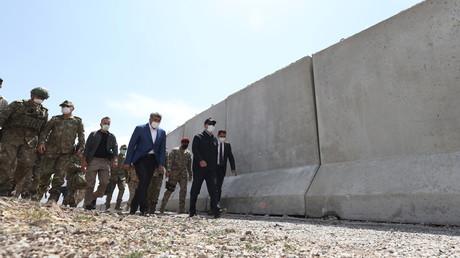Le ministre turc de la Défense, Hulusi Akar, inspecte une portion de mur à la frontière entre la Turquie et l'Iran, dans la province de Van, le 14 août 2021.