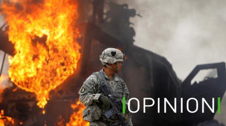 Un officier américain se tient devant un véhicule militaire M-ATV en flammes dans la vallée de Kandahar, en Afghanistan, en juillet 2010 (image d'illustration).