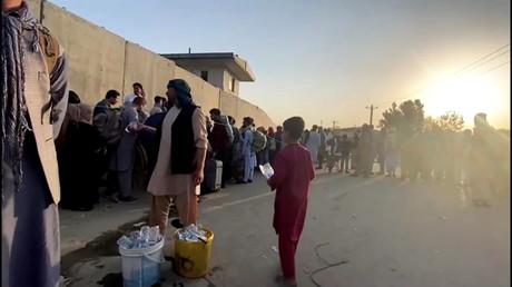 Un homme demande aux gens de faire la queue alors qu'ils se tiennent devant l'aéroport de Kaboul (image d'illustration).