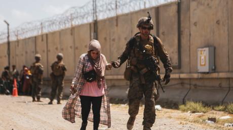Un Marine américain  assiste une femme lors d'une évacuation à l'aéroport de Kaboul, en Afghanistan, le 22 août 2021.