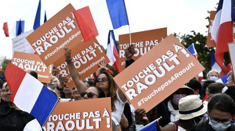 Des manifestants tiennent des banderoles en soutien à Didier Raoult, lors d'une manifestation à Paris le 21 août 2021 (image d'illustration).