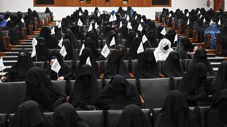 Des étudiantes voilées brandissent les drapeaux des Taliban alors qu'elles écoutent un orateur avant un rassemblement pro-Taliban à l'université d'éducation Shaheed Rabbani à Kaboul, le 11 septembre 2021.