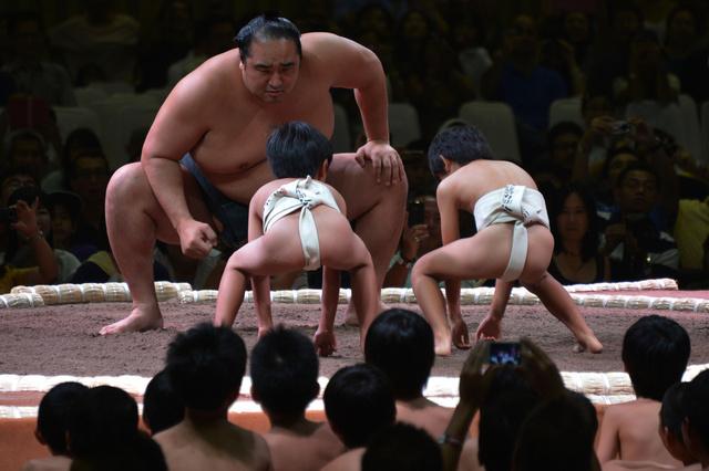أندونيسيا- جاكارتا:  مدرب ياباني بمصارعة السومو في نزال وهمي (استعراضي) مع اثنين من الأطفال، قبل يومين على انطلاق بطولة العالم لمصارعة السومو في جاكارتا بشهر أغسطس/ آب 2013.