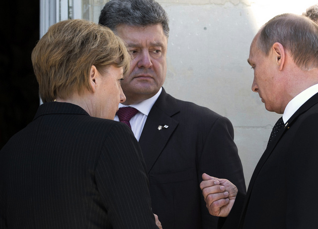 بوتين يتحدث مع بوروشينكو أثناء توجهه الى الغداء على هامش لقاءاته في فرنسا
