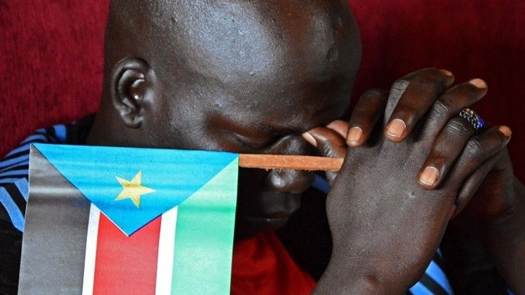 شاب جنوب سوداني يحمل علم بلاده