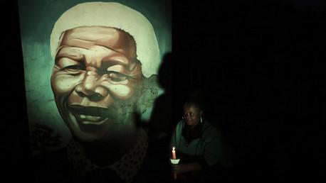 مواطن إفريقي جنوبي يمسك شمعة في يده أمام صورة الرئيس الراحل نيلسون مانديلا