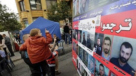 أطفال ينظرون إلى صور جنود لبنانيين مختطفين لدى المتطرفين
