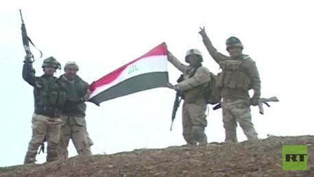 جنود عراقيون يرفعون العلم بعد هزيمتهم لمسلحي داعش