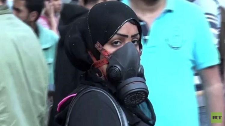 مصرية تضع على وجهها قناعة ضد الغاز أثناء المظاهرات