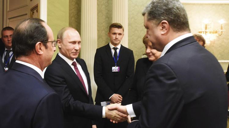 الرئيس بوتين يصافح نظيره الأوكراني بيوتر بوروشينكو في حضور هولاند وميركل