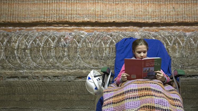 طفلة تقرأ كتاب داخل منتجع بيلاروسيا الصحي بالقرب من مدينة سوليغورسك، جنوب مينسك