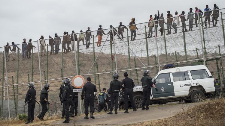مهاجرون أفارقة يتسلقون السياج الحديدي بحضور الشرطة الإسبانية بمدينة مليلة، 17 مايو/آذار 2014