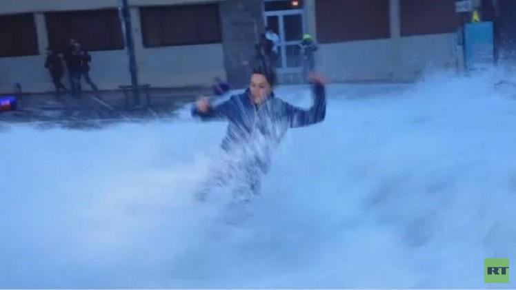 بالفيديو..موجة ضخمة تسقط مراسلة أثناء البث المباشر