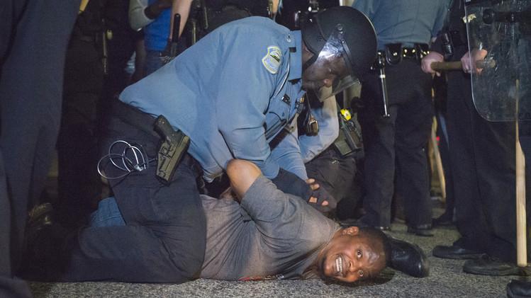قوات الشرطة تلقي القبض على أحد المتظاهرين خارج مركز الشرطة في المدينة، 11 مارس 2015