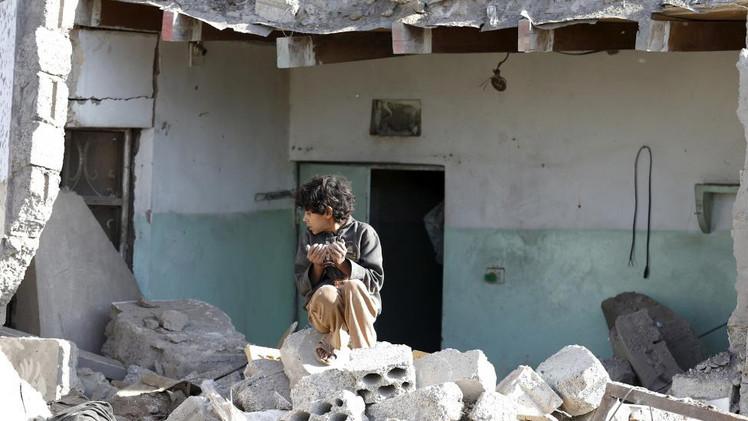 طفل يجلس فوق أطلال مبنى سكني أصابته الضربات الجوية بالقرب من مطار صنعاء، 26 مارس