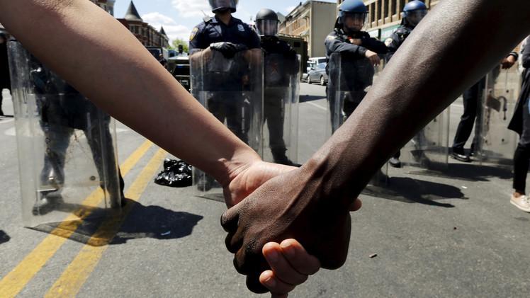 متظاهران أبيض وأسود يمسكان بأيدي بعضهما البعض لإعلان تضامن البيض مع السود ضد عنف الشرطة، 28 أبريل