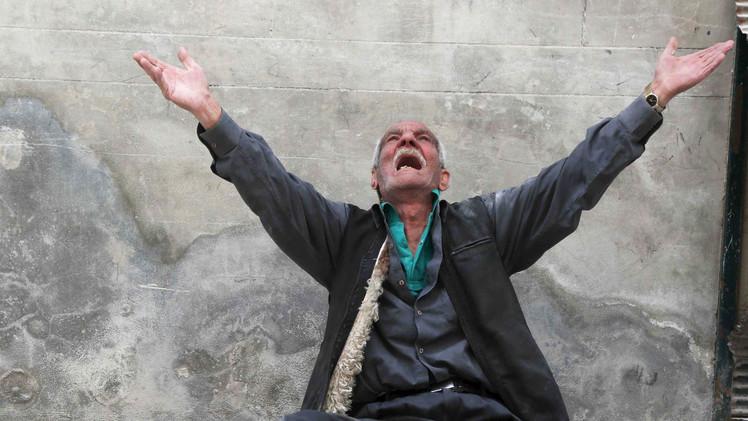 عجوز يتضرع للسماء من بين الأنقاض في حلب،أبريل 2015