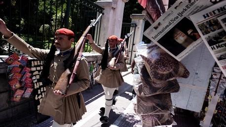 الحرس الرئاسي اليوناني يمر أمام كشك لبيع الصحف في أثينا في 7 يوليو 2015