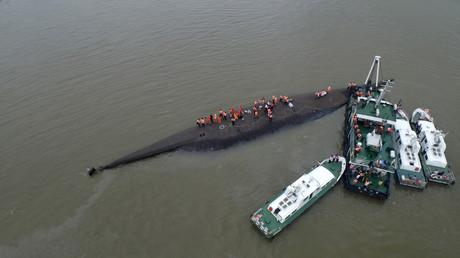 أفراد من فرقة الإنقاذ أثناء بحثهم عن سفينة غرقت في نهر في الصين