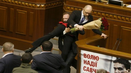 النائب أوليغ بارنا الأوكراني يبعد رئيس الوزراء ارسيني ياتسينيوك من على المنبر، بعد أن قدم له باقة من الورود، خلال جلسة البرلمان (رادا) في كييف، أوكرانيا، 11 ديسمبر، 2015