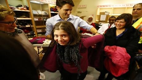 رئيس وزراء كندا جاستن ترودو يساعد فتاة لاجئة سورية في ارتداء معطف شتوي بعد أن وصلت مع عائلتها من بيروت في مطار تورونتو بيرسون الدولي في ميسيسوجا، أونتاريو، كندا 11 ديسمبر 2015