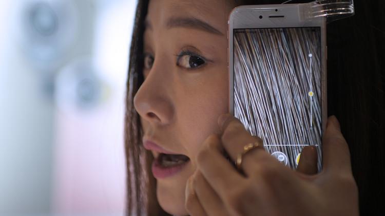 سيدة تختبر كاميرا متناهية الصغر، يمكن تثبيتها على هاتف آيفون، وتعرض الكاميرا خصلات متناهية الصغر من شعرها، في ثالث أيام معرض الجوال العالمي، برشلونة، إسبانيا، 24 فبراير/شباط 2016