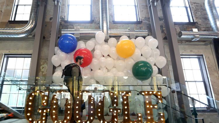 رجل يسير وسط الأضواء والبالونات التي استخدمت في افتتاح مكتب شركة غوغل الجديد في كندا