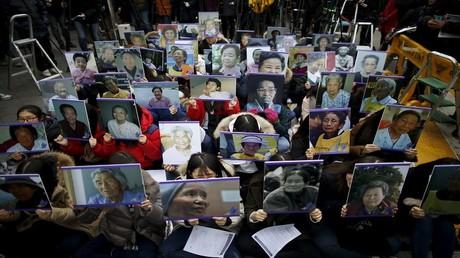 طلاب كوريون يحتجون أمام السفارة اليابانية في سيئول في 30 ديسمبر 2015، حاملين صورا لنساء كانوا قد أجبروا على تقديم خدمات جنسية في الحرب العالمية الثانية للترفيه عن أفراد الجيش الياباني.