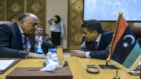 وزير الخارجية المصري سامح شكري يتحدث مع نظيره الليبي محمد الديري خلال اجتماع طارئ لوزراء الخارجية العرب في العاصمة المصرية القاهرة، في 24 ديسمبر 2015