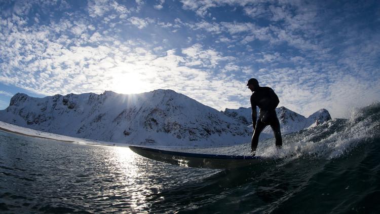 ركمجي (رياضي راكب موج) ينزلق على موجة بالقرب من شاطئ مكسو بالثلج