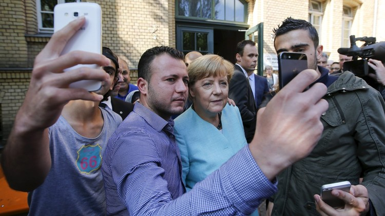 لاجئون من سوريا والعراق يلتقطون سيلفي مع أنغيلا ميركل
