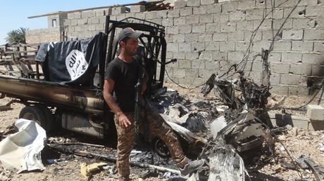جندي عراقي قرب عربة مدمرة لداعش في هيت