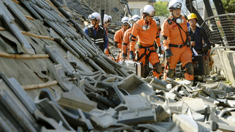رجال الإطفاء بين المنازل المهدمة بفعل الزلزال في بلدة Mashiki، مقاطعة كوماموتو، اليابان