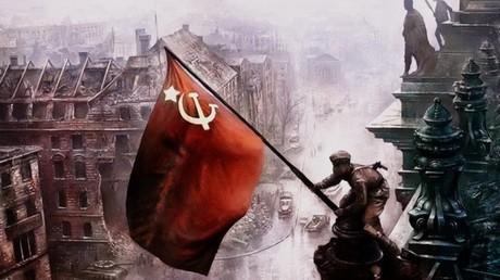 جندي سوفيتي يرفع راية النصر فوق مبنى الرايخستاغ الألماني في برلين.